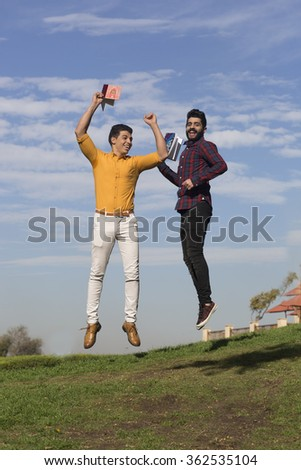 Jumping in excitement/Two Arabic models jumping on air and looking happy in the garden and holding books