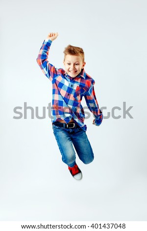 Jumping little boy in the colorful plaid shirt, blue jeans, gumshoes. Isolated. - stock photo