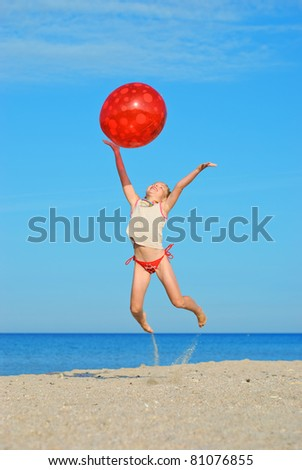 Jumping little girl with red ball on the beach - stock photo