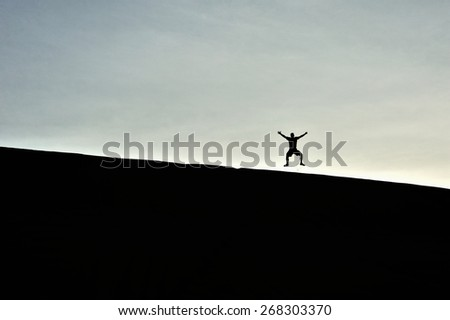 jumping man on the sand on the sunrise in Vietnam - stock photo