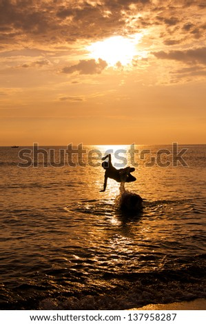 Jumping man silhouette in golden sunrise hours with the sea background in Phu Yen beach.