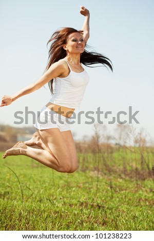 Jumping  mid adult woman  against summer meadow