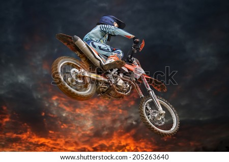 Jumping motocross rider with firestorm in the background and red glowing spinning rear wheel - stock photo