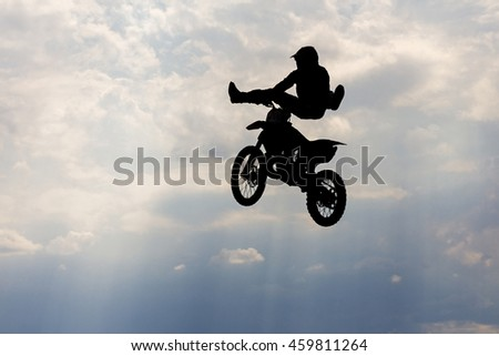 Jumping motorcircle rider silhouette on sky background.