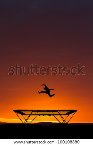 jumping on trampoline in sunset - stock photo