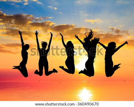 Jumping over Sunset Backlit Group  - stock photo
