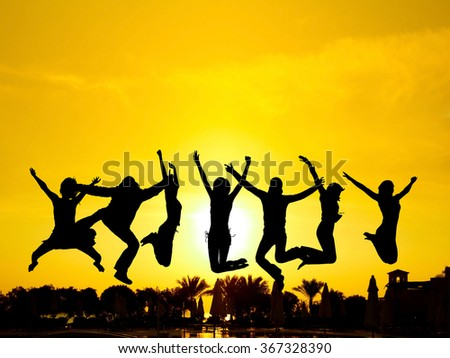 Jumping over Sunset Evening Celebration  - stock photo