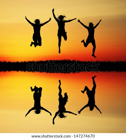 Jumping people at sunset - stock photo