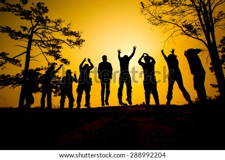 Jumping Silhouette people group team in Sunset time - stock photo