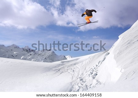Jumping skier at jump in high mountains at sunny day