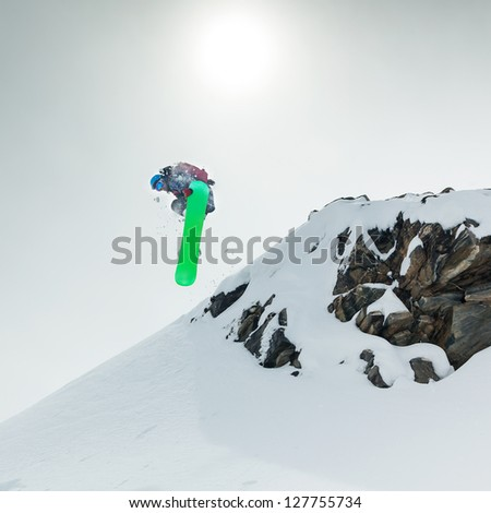 Jumping snowboarder in mountains on the snowboard - stock photo