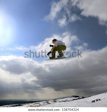 Jumping snowboarder in mountains on the snowboard on blue sky background - stock photo