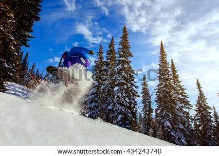 Jumping snowboarder on snowboard in mountains in ski resort on blue sky background - stock photo