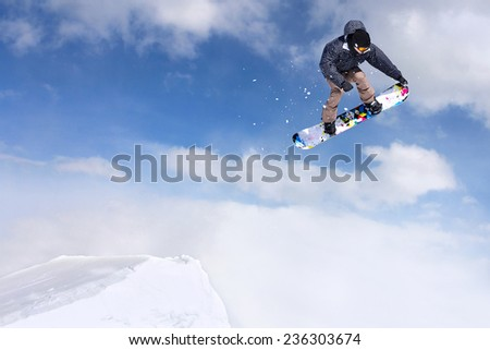 Jumping snowboarder through air on blue sky background - stock photo