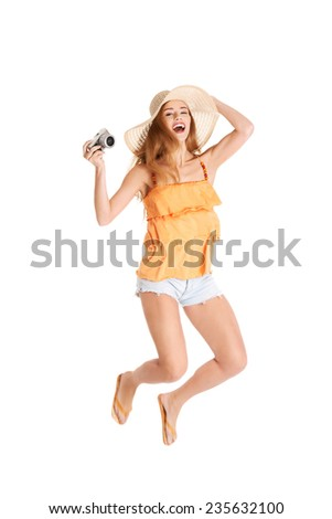 Jumping woman holding a camera. - stock photo