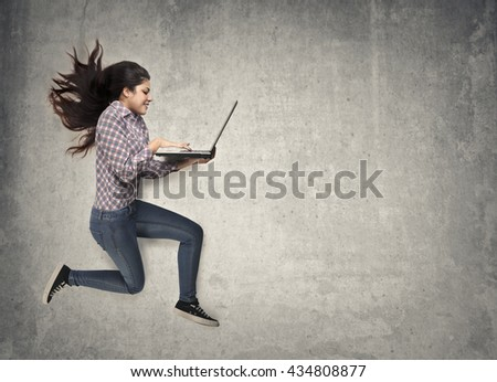 Jumping woman holding a pc