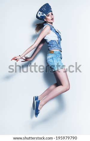 jumping woman in blue denim shorts and hat - stock photo