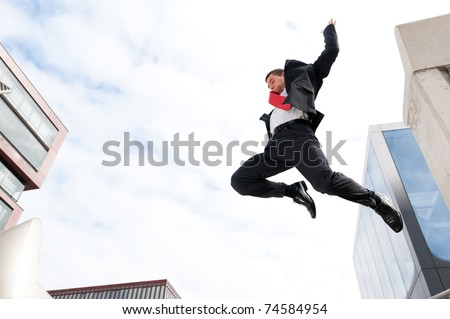 Jumping young buiness man in front of buildings - stock photo