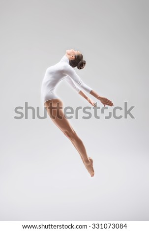 Jumping young gymnast in studio - stock photo