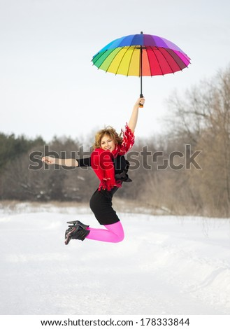 Jumpling young woman with multicolor umbrella at winter forest - stock photo
