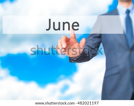 June - Businessman hand touch  button on virtual  screen interface. Business, technology concept. Stock Photo