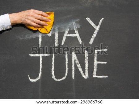 June is coming concept - inscription May and June on a school blackboard, with the words June being erased by the teacher. - stock photo
