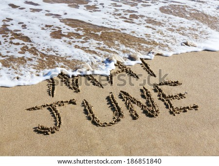 June is coming concept - inscription May and June written on a sandy beach, the wave is starting to cover the word May.  - stock photo