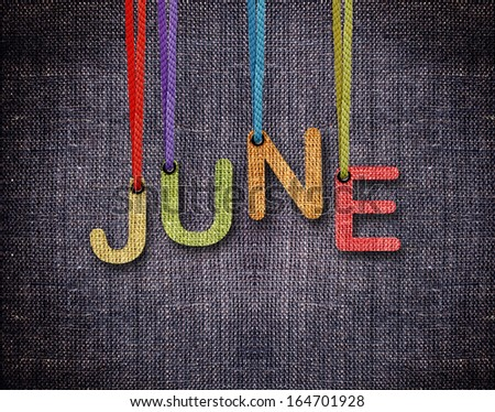 June letters hanging strings with blue sackcloth background. - stock photo