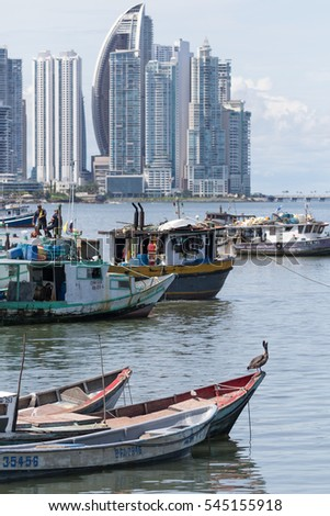 June 15, 2016 Panama City, Panama:  a pelican is standing on a small fishing boat floating on the water by the fish market with the modern downtown highrise buildings in the background