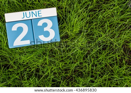 June 23rd. Image of june 23 wooden color calendar on green grass lawn background. Summer day, empty space for text.