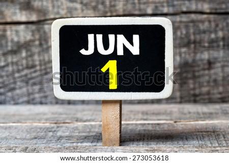June 1 written on blackboard on a wooden background - stock photo