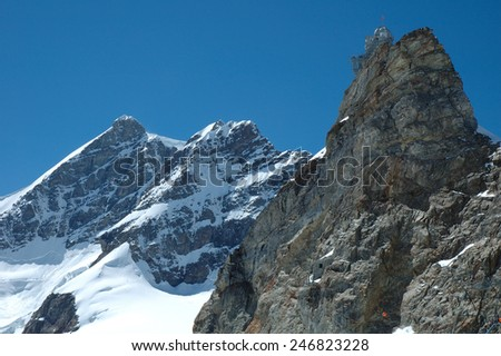 Jungfrau peak and Sphinx Observatory on rock on Jungfraujoch pass in Alps in Switzerland - stock photo