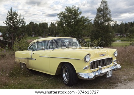 JUNGFRUKUSTEN, SWEDEN ON JULY 18. View of a yellow Chevrolet Bel Air on July 18, 2012 in Norrfjarden, Sweden. Cloudy evening, forest in the background.