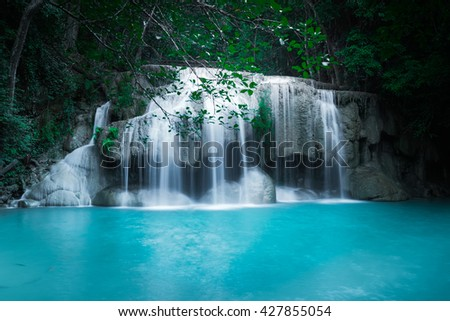 Jungle landscape with flowing turquoise water of Erawan cascade waterfall at deep tropical rain forest. National Park Kanchanaburi, Thailand - stock photo