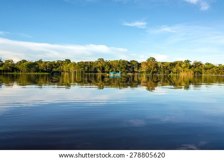 Jungle, sky, and boat reflected in the clear blue water of the Javari River in the Brazilian Amazon Rainforest - stock photo