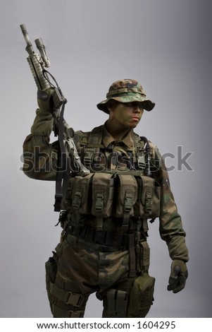 jungle soldier in the army dressed in camo holding gun up - stock photo