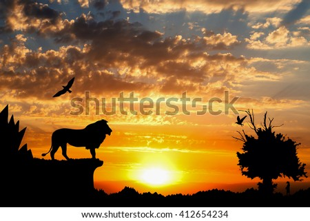 Jungle with mountains, old tree, birds lion and meerkat on golden cloudy sunset background - stock photo