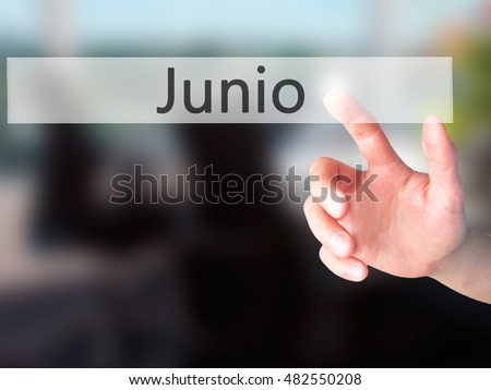 Junio (June in Spanish) - Hand pressing a button on blurred background concept . Business, technology, internet concept. Stock Photo