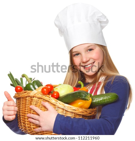 junior cook holding a basket full of vegetables and thumbs up - stock photo