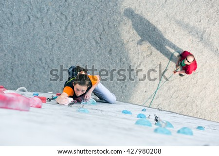 Junior female Athlete climbs Competition route and belaying referee watching her from below. Dnipro, Ukraine, May 21, 2016 - stock photo