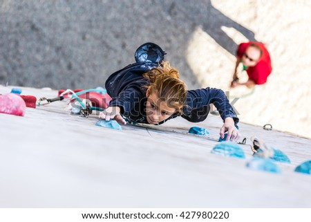 Junior female Athlete climbs Competition route and belaying referee watching her from below. Dnipro, Ukraine, May 20, 2016 - stock photo