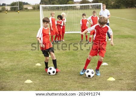 Junior football team training with coach - stock photo