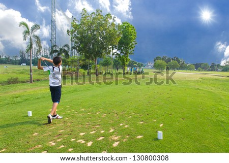 Junior golfer driving golf ball on golf course - stock photo