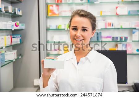 Junior pharmacist showing medicine box at the hospital pharmacy - stock photo