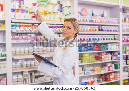 Junior pharmacist taking medicine from shelf in the pharmacy - stock photo
