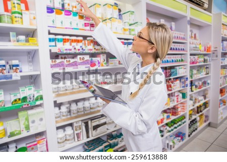 Junior pharmacist taking medicine from shelf in the pharmacy - stock photo