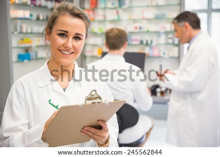 Junior pharmacist writing on clipboard at the hospital pharmacy