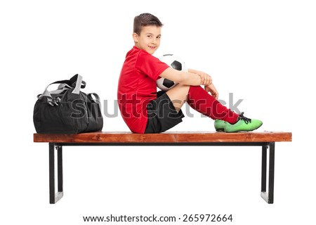 Junior soccer player in a red jersey, holding a ball and sitting on a wooden bench isolated on white background - stock photo