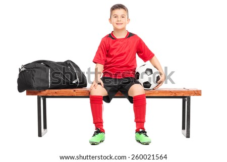 Junior soccer player sitting on a bench and holding a football isolated on white background - stock photo