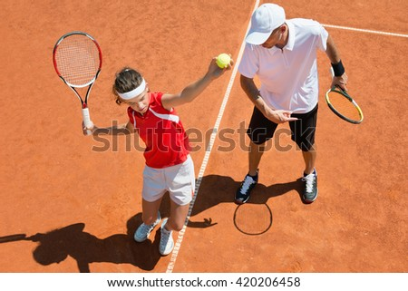 Junior tennis player practicing service with tennis coach - stock photo
